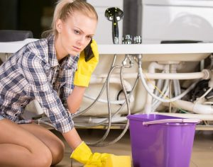 woman cleaning up a water leak occured in her bathroom, calling Palm Bay Plumbing Services water leak detection and repair services in Palm Bay, Melbourne, and The Beaches