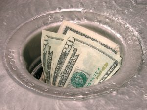 dollar signs are stuck in the garbage disposal, symbolizing the need for garbage disposal services in Palm Bay - Melbourne Florida